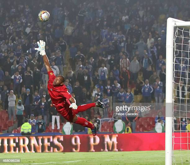 Luis Estacio goalkeeper of Boyaca Chico FC jumps to catch the ball as Maximiliano Nuñez of Millonarios scores the third goal of his team during a...