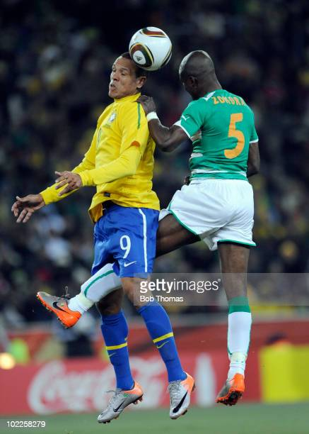Luis Fabiano of Brazil heads the ball with Didier Zokora of the Ivory Coast during the 2010 FIFA World Cup South Africa Group G match between Brazil...