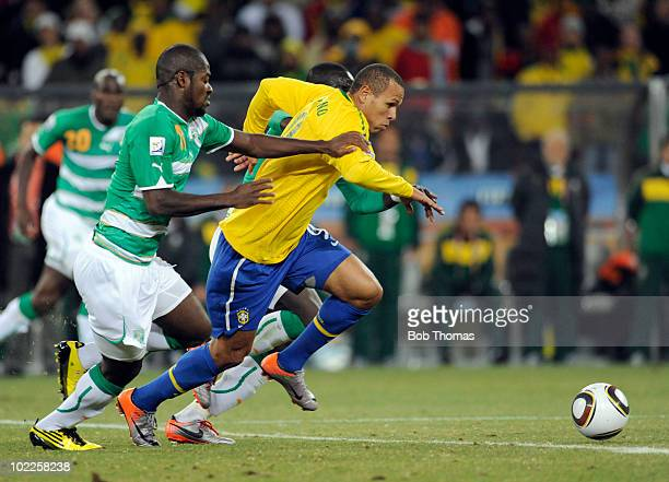Luis Fabiano of Brazil is challenged by Romaric of the Ivory Coast during the 2010 FIFA World Cup South Africa Group G match between Brazil and Ivory...