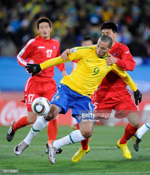 Luis Fabiano of Brazil is held by Ri Kwang Chon of North Korea during the 2010 FIFA World Cup South Africa Group G match between Brazil and North...