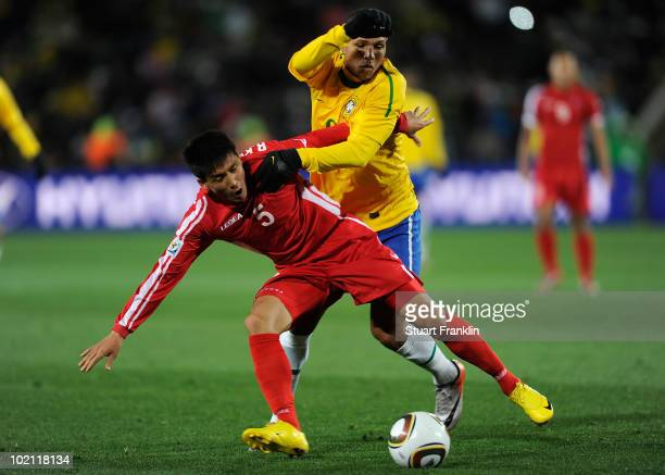 Luis Fabiano of Brazil is tackled by Ri KwangChon of North Korea during the 2010 FIFA World Cup South Africa Group G match between Brazil and North...