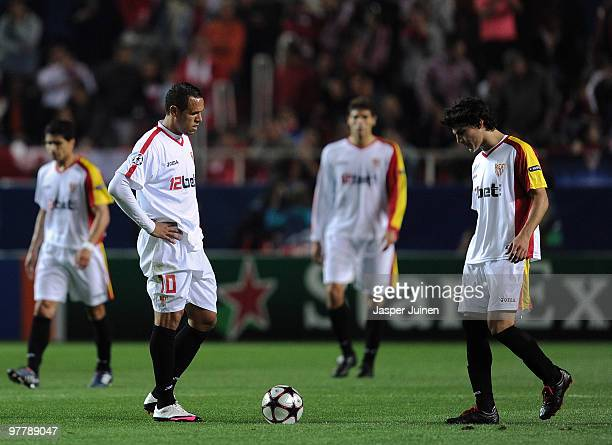 Luis Fabiano of Sevilla stands dejected with his team mates after conceding a goal during the UEFA Champions League round of sixteen second leg match...