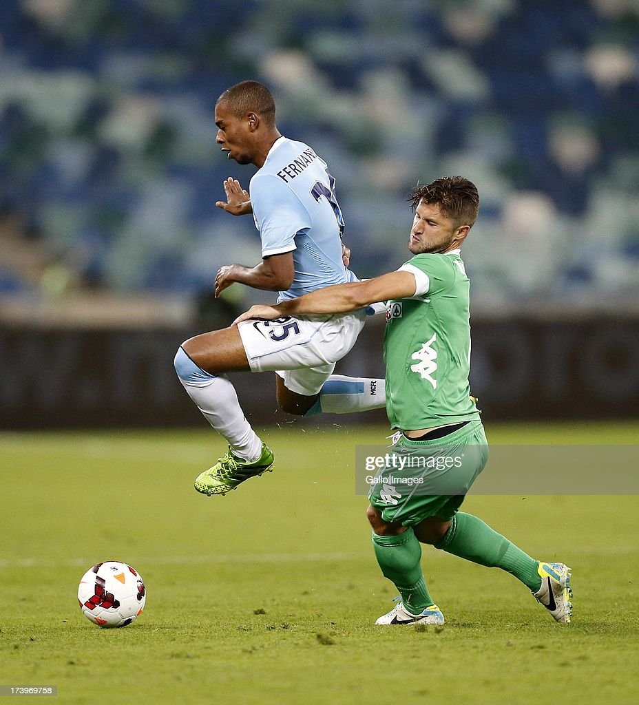 Luis Fernandinho of Manchester City battles with Marc van Heerden of Amazulu during the Nelson Mandela Football Invitational match between AmaZulu and Manchester City at Moses Mabhida Stadium on July 18, 2013 in Durban, South Africa.
