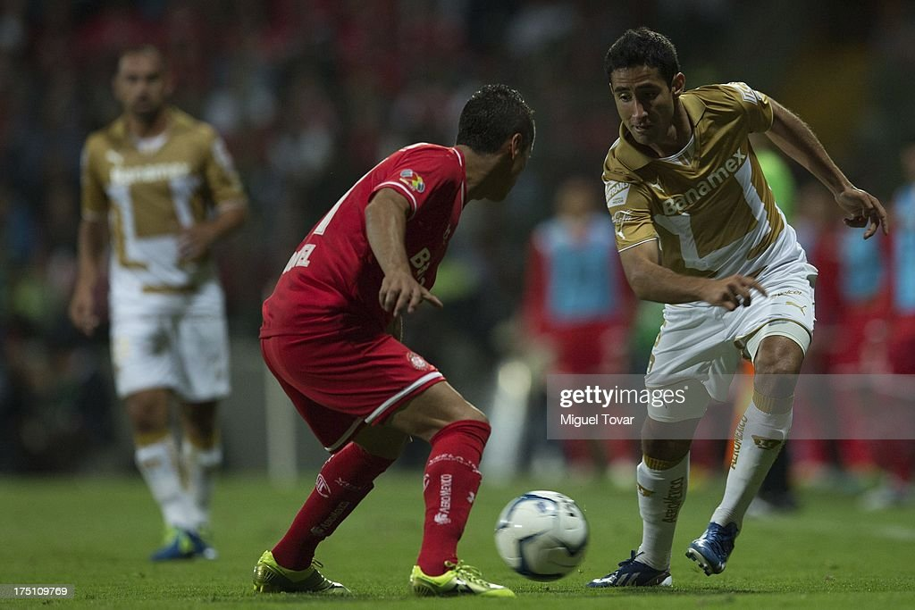 Luis Fernando Fuentes of Pumas drives the ball as Carlos Esquivel of Toluca defends during a match between Toluca and Pumas as part of the Torneo Apertura 2013 Liga MX at Nemesio Siez stadium, on July 31, 2013 in Toluca, Mexico.