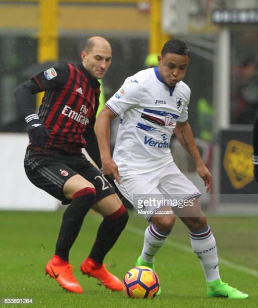 Luis Fernando Muriel of UC Sampdoria is challenged by Gabriel Paletta of AC Milan during the Serie A match between AC Milan and UC Sampdoria at...