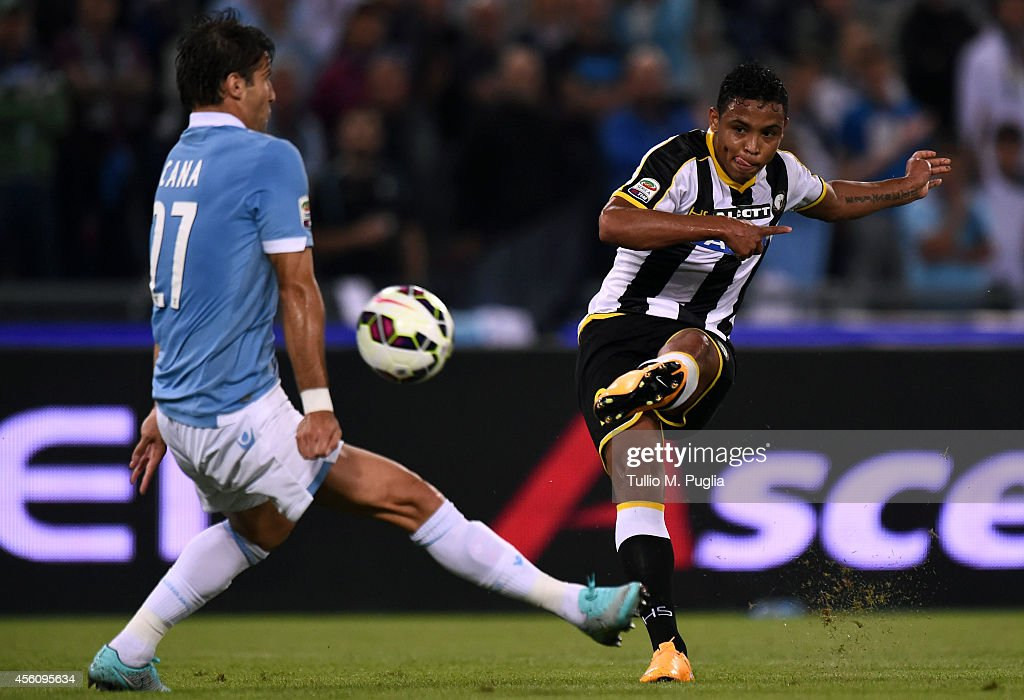 Luis Fernando Muriel (R) of Udinese kicks the ball as Lorik Cana of Lazio tackles compete for the ball during the Serie A match between SS Lazio and Udinese Calcio at Stadio Olimpico on September 25, 2014 in Rome, Italy.
