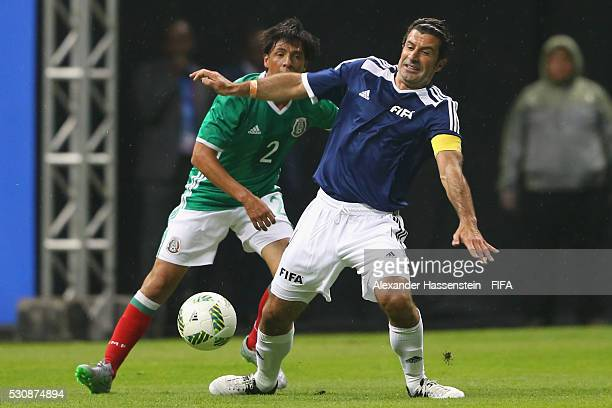Luis Figo of FIFA Legends battles for the ball with Alberto Rodriguez of MexicanAllstars during an exhibition match between FIFA Legends and...