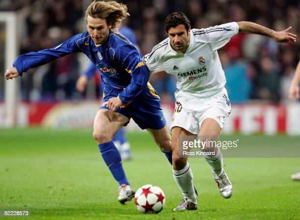 Luis Figo of Real Madrid is challenged by Pavel Nedved of Juventus during the UEFA Champions League match between Real Madrid and Juventus at The...