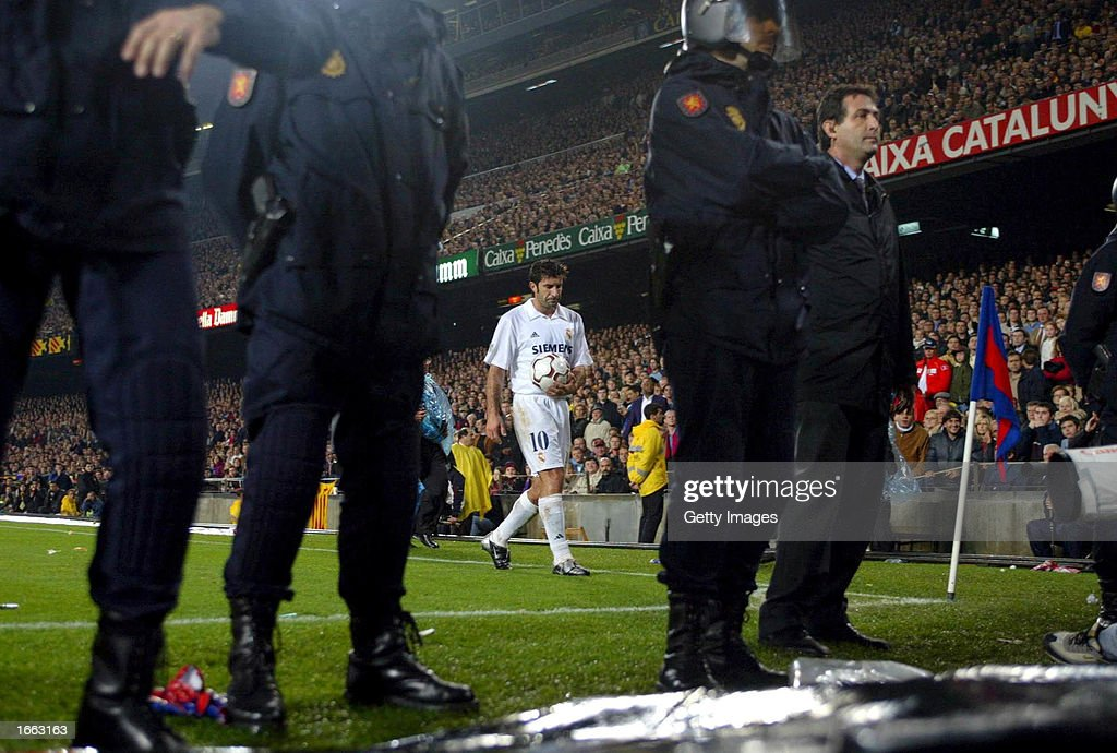 Luis Figo of Real Madrid prepares to take a corner with a police escort during the La Liga match between FC Barcelona and Real Madrid played at the...