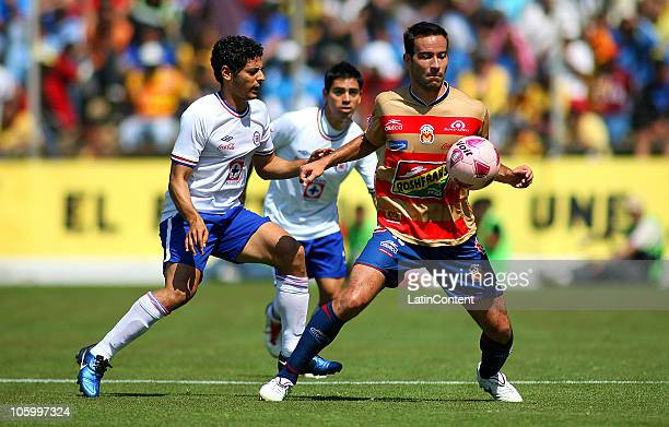 Luis Gabriel Rey of Morelia vies for the ball with Alejandro Vela of Cruz Azul during their match as part of the Apertura 2010 at Morelos Stadium on...