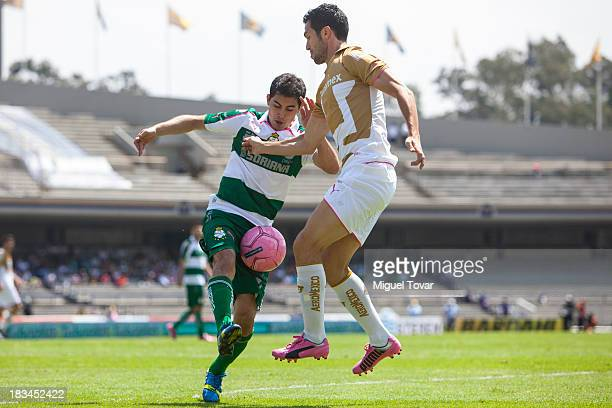 Luis Garcia of Pumas fights for the ball with Oswaldo Alanis of Santos during a match between Pumas and Santos as part of the Apertura 2013 Liga MX...