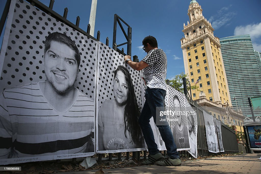 Luis Gomez attaches pictures to a fence near the Freedom Tower as he helps hang the 'Inside Out 11M' project on August 31, 2013 in Miami, Florida. The public art project puts a face on immigration reform by creating a massive mosaic of portraits taken on site, printed immediately and pasted on the Freedom Tower at Miami-Dade College.