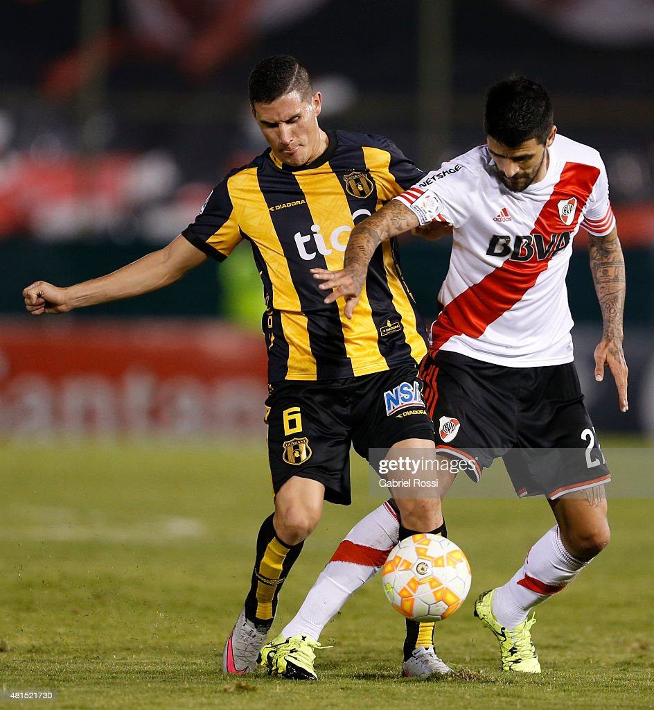 Luis Gonzalez of River Plate (R) fights for the ball with Jorge Mendoza of Guarani (L) during a second leg Semi Final match between Guarani and River Plate as part of Copa Bridgestone Libertadores 2015 at Defensores del Chaco Stadium on July 21, 2015 in Asuncion, Paraguay.