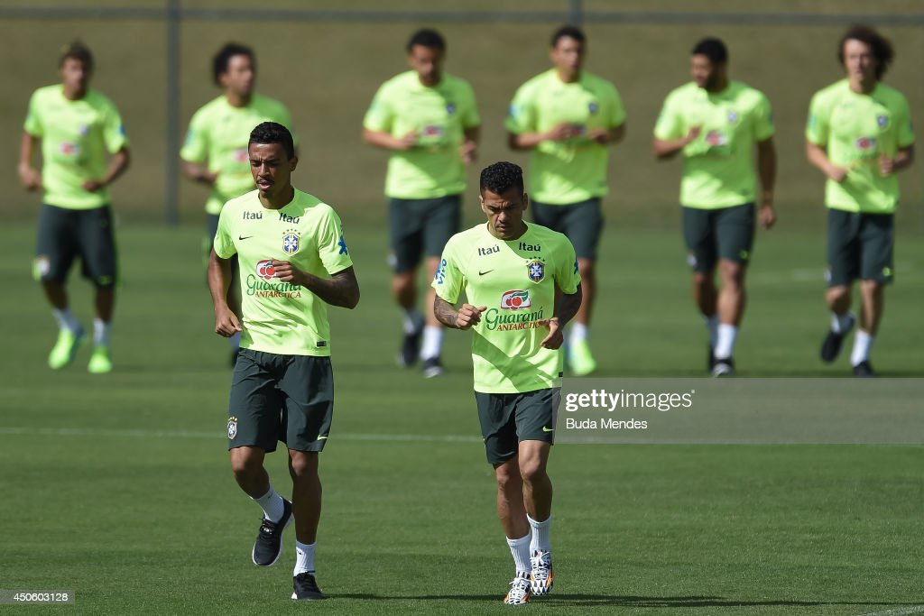 Luis Gustavo (L) and Daniel Alves run during a training session of the Brazilian national football team at the squad's Granja Comary training complex, on June 14, 2014 in Teresopolis, 90 km from downtown Rio de Janeiro, Brazil.