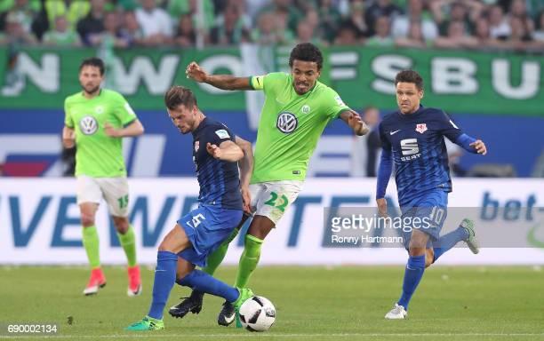 Luis Gustavo of Wolfsburg competes with Quirin Moll and Mirko Boland of Braunschweig during the Bundesliga Playoff first leg match between VfL...