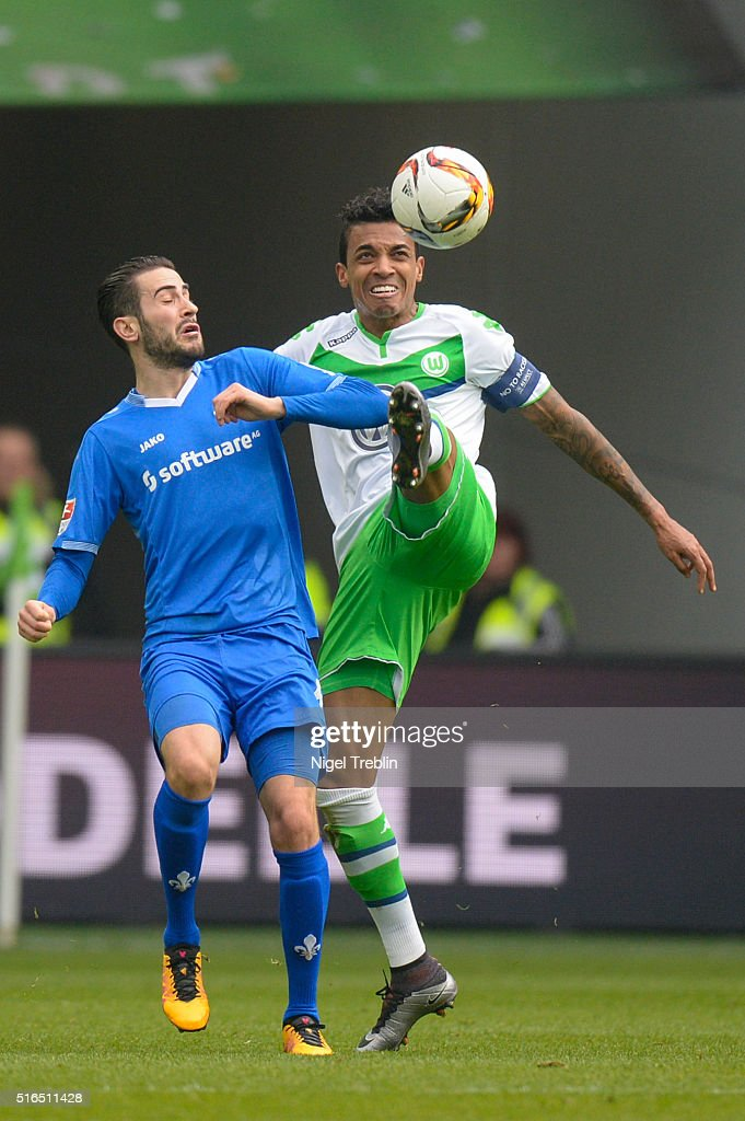 Luis Gustavo of Wolfsburg is challenged by Jerome Gondorf of Darmstadt the Bundesliga match between VfL Wolfsburg and Hertha BSC Berlin at Volkswagen Arena on March 19, 2016 in Wolfsburg, Germany.