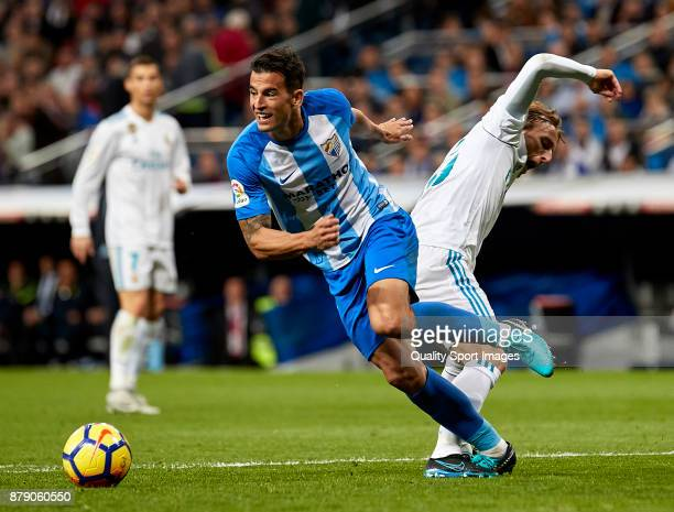 Luis Hernandez of Malaga CF is challenged by Luka Modric of Real Madrid during the La Liga match between Real Madrid and Malaga at Estadio Santiago...
