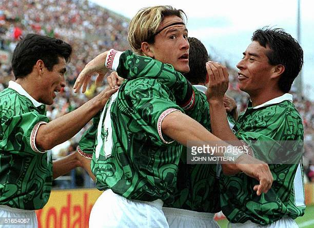 Luis Hernandez of Mexico celebrates with teammates Benjamin Galindo and Luis Roberto Alves after Hernandez scored his team's second goal in the...