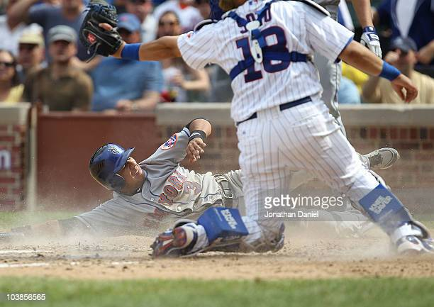 Luis Hernandez of the New York Mets looks up at the umpire after sliding into home past the tag attempt of Geovany Soto of the Chicago Cubs to score...