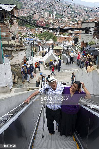 Luis Holguin takes the escalators with his crutch and his daughter Resfa Holguin at Comuna 13 neighborhood in Medellin Antioquia department Colombia...