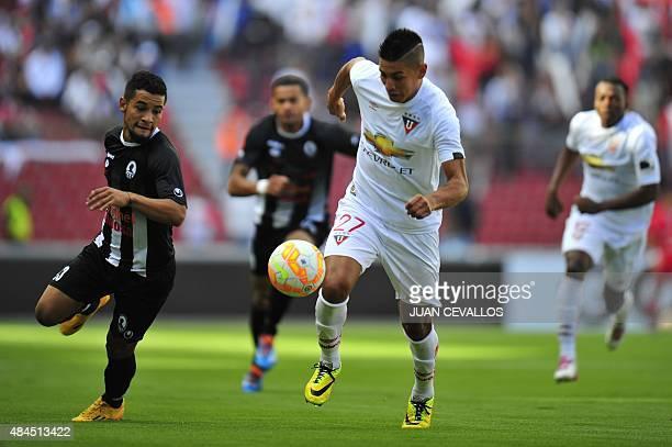 Luis Manuel Romero of Ecuador's Liga de Quito vies for the ball with Cesar Enrique Martinez Quintero of Venezuela's Zamora during their Copa...