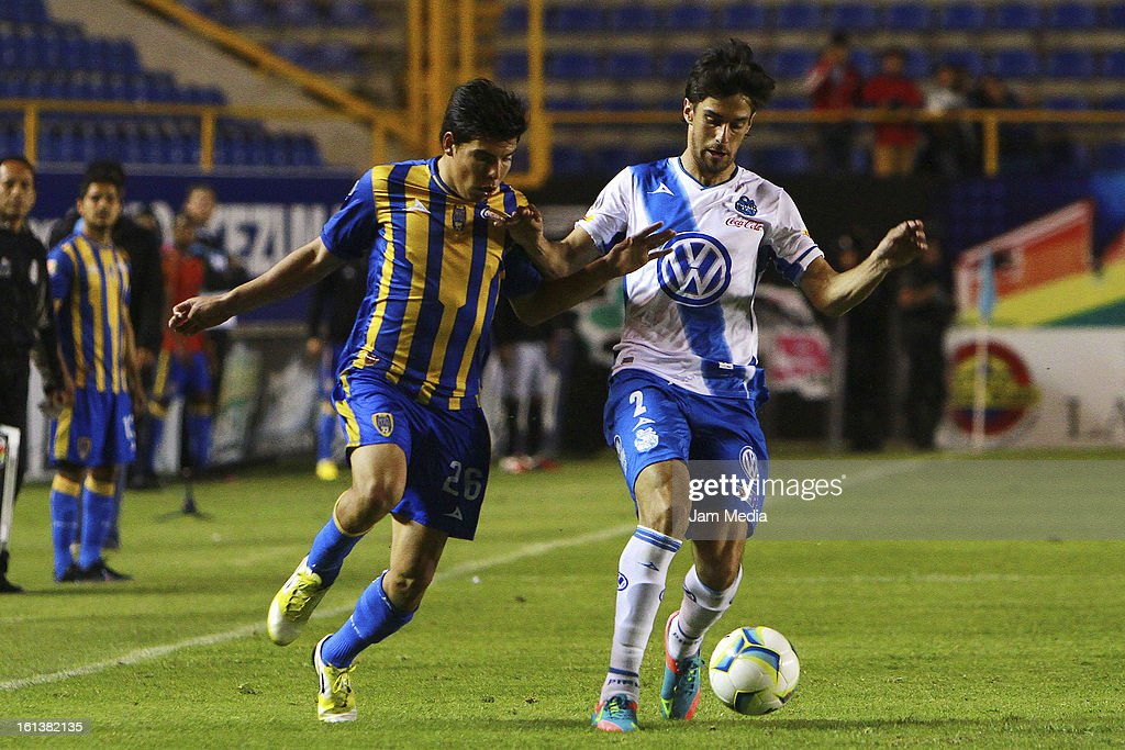 Luis Mendoza (L) of San Luis struggles for the ball with Jonathan Lacerda (R) of Puebla during a match between San Luis and Puebla as part of the Clausura 2013 Liga MX at Alfonso Lastras Stadium on February 09, 2013 in San Luis Potosi, Mexico.