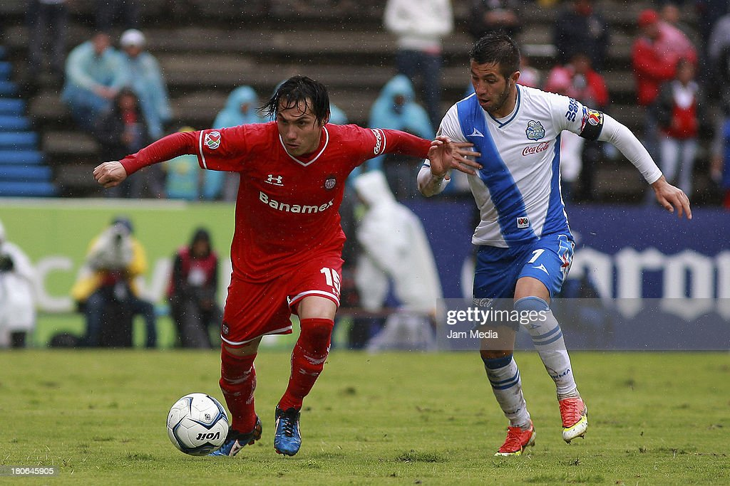 Luis Miguel Noriega (R) of Puebla struggles for the ball with Antonio Rios (L) of Toluca during a match as part of Apertura 2013 Liga MX at Cuauhtemoc Stadium on September 14, 2013 in Puebla, Mexico.