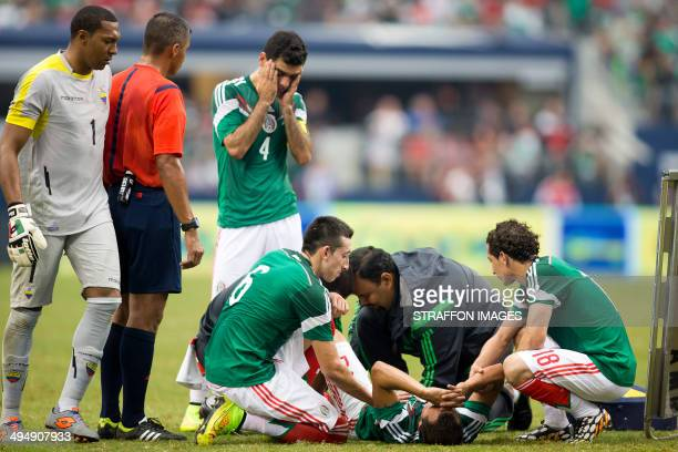 Luis Montes of Mexico lies injured with a broken leg as his team mate Rafael Marquez shows concern during the International Friendly match between at...