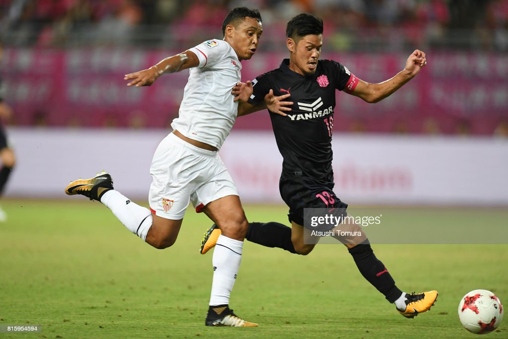 Luis Muriel of Sevilla FC (L) and Hotaru Yamaguchi of Cerezo Osaka (R) compete for the ball during the preseason friendly match between Cerezo Osaka and Sevilla FC at Yanmar Stadium Nagai on July 17, 2017 in Osaka, Japan.