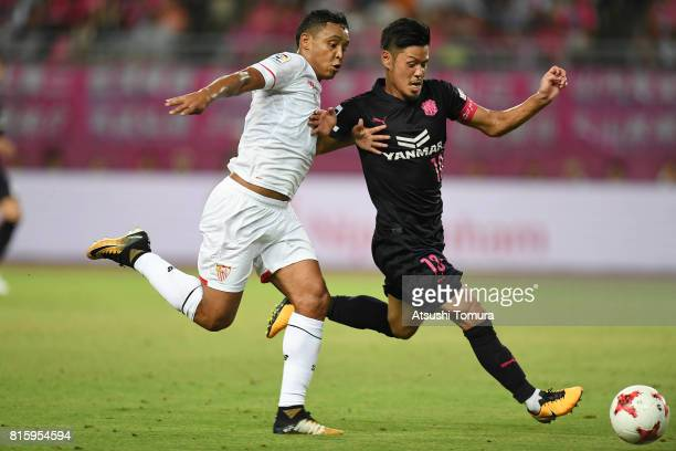 Luis Muriel of Sevilla FC and Hotaru Yamaguchi of Cerezo Osaka compete for the ball during the preseason friendly match between Cerezo Osaka and...