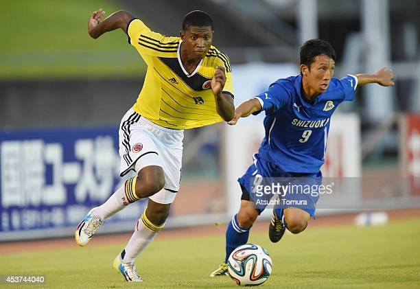 Luis Orejuela of Colombia is challenged by Haruhi Kotani of Shizuoka in the U19 match between Shizuoka Youth selections and Colombia during SBS Cup...