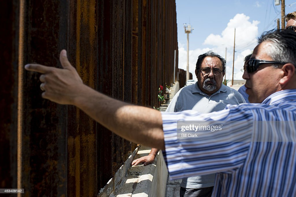 Luis Parra, attorney representing the mother of Jose Antonio Elena Rodriguez, a Mexican teenager who was shot by U.S. Border Patrol agents in 2012, talks about the case to Rep. Raul Grijalva, D-Ariz., and staff at the spot of the shooting in Nogales, Ariz., on Friday, Aug. 8, 2014. A U.S. Border Patrol vehicle and a border surveillance tower can be seen in the background.