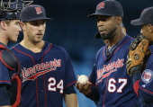 Luis Perdomo of the Minnesota Twins and Trevor Plouffe and Chris Hermann and Alexi Casilla during a conference on the mound during MLB game action...