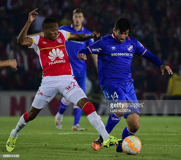 Luis Quiñones of Colombia's Santa Fe vies for the ball with Gonzalo Porras of Uruguay's Nacional during their 2015 Sudamericana Cup football match...