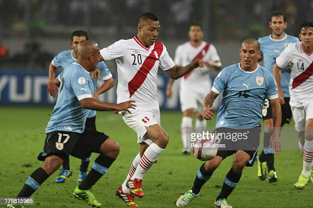 Luis Ramirez of Peru fights for the ball with Egidio Arevalo Rios and Maximiliano Pereira of Uruguay during a match between Peru and Uruguay as part...