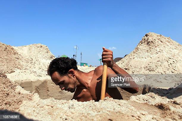 Luis Reyes digs a hole at the beach on a hot afternoon at Coney Island on August 31 2010 in the Brooklyn borough of New York City Reyes enjoys...