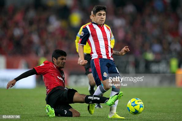 Luis Robles of Atlas slides for the ball as Javier Lopez of Chivas tries to dribble during the 6th round match between Atlas and Chivas as part of...