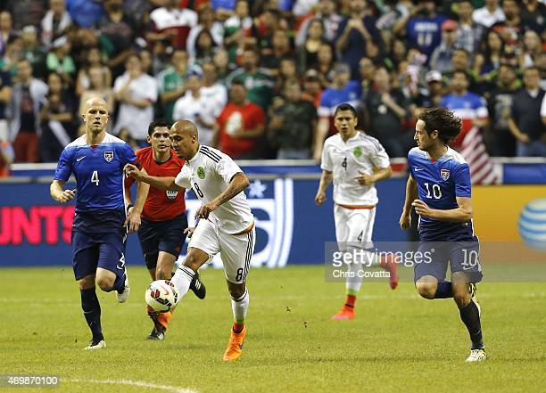 Luis Rodriguez of Mexico advances the ball between Michael Bradley and Mix Diskerud of the United States during an international friendly match at...