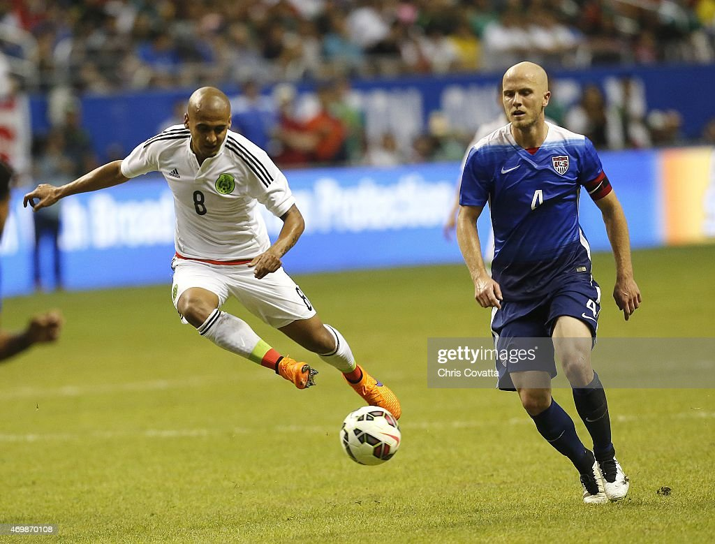 Luis Rodriguez #8 of Mexico kicks the ball as <a gi-track='captionPersonalityLinkClicked' href=/galleries/search?phrase=Michael+Bradley+-+Soccer+Player&family=editorial&specificpeople=7022299 ng-click='$event.stopPropagation()'>Michael Bradley</a> #4 of the United States tries to defend during an international friendly match at the Alamodome on April 15, 2015 in San Antonio, Texas.
