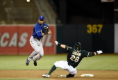 Luis Sardinas of the Texas Rangers completes the doubleplay over the top of Eric Sogard of the Oakland Athletics in the bottom of the six inning at...