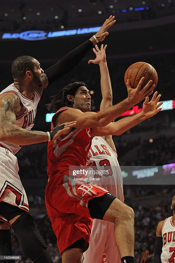 Luis Scola #4 of the Houston Rockets drives between Carlos Boozer #5 and Joakim Noah #13 of the Chicago Bulls at the United Center on April 2, 2012 in Chicago, Illinois.