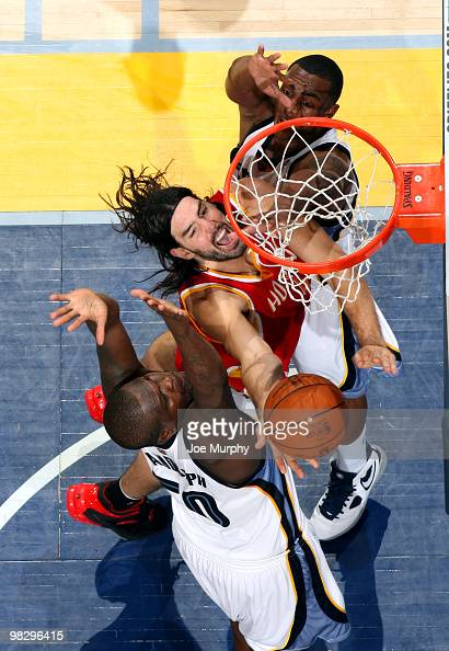 Luis Scola of the Houston Rockets shoots a layup between Zach Randolph and Darrell Arthur of the Memphis Grizzlies on April 06 2010 at FedExForum in...
