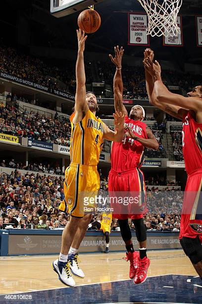 Luis Scola of the Indiana Pacers shoots against Dante Cunningham of the New Orleans Pelicans on December 23 2014 at Bankers Life Fieldhouse in...