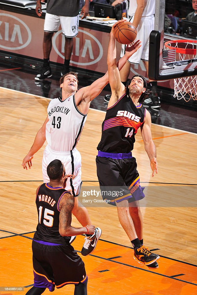 Luis Scola #14 of the Phoenix Suns and Kris Humphries #43 of the Brooklyn Nets reach for a rebound on March 24, 2013 at U.S. Airways Center in Phoenix, Arizona.