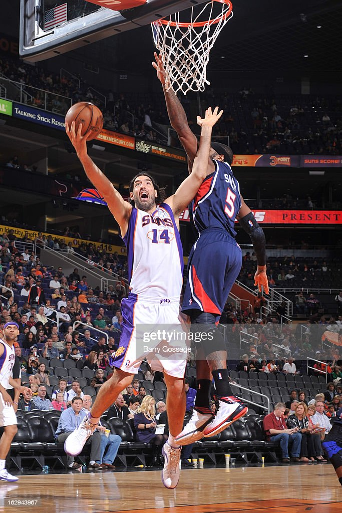 Luis Scola #14 of the Phoenix Suns drives for a shot against Josh Smith #5 of the Atlanta Hawks on March 1, 2013 at U.S. Airways Center in Phoenix, Arizona.