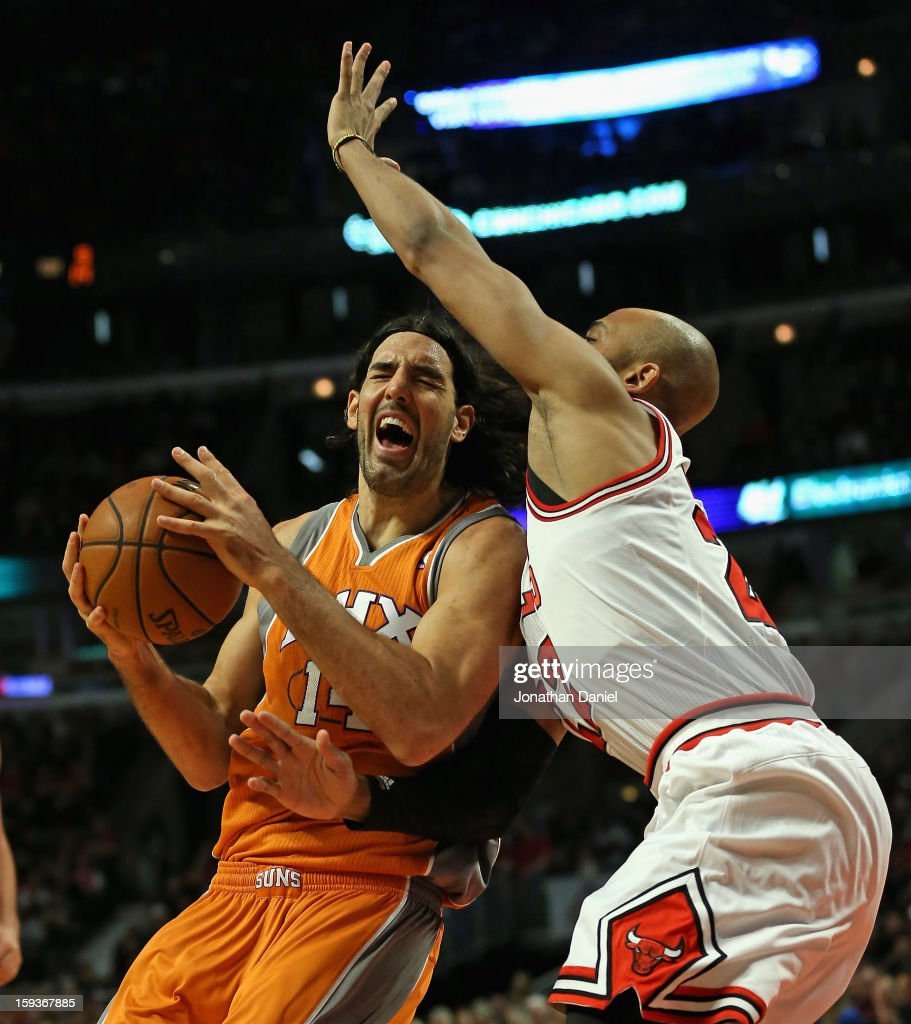 Luis Scola #14 of the Phoenix Suns is fouled by Taj Gibson #22 of the Chicago Bulls at the United Center on January 12, 2013 in Chicago, Illinois.