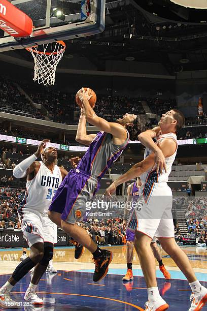 Luis Scola of the Phoenix Suns shoots against Byron Mullens and Brendan Haywood of the Charlotte Bobcats at the Time Warner Cable Arena on November 7...