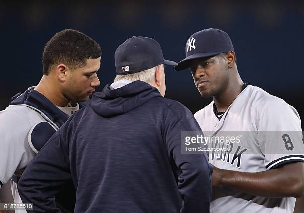 Luis Severino of the New York Yankees is visited on the mound by pitching coach Larry Rothschild as Gary Sanchez looks on in the first inning during...