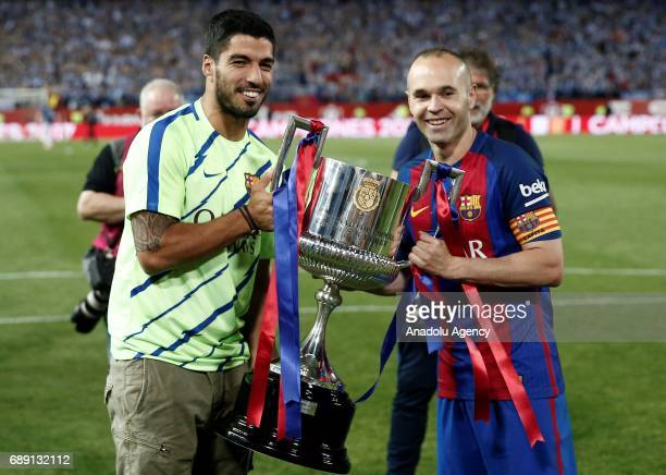 Luis Suarez and Andres Iniesta of Barcelona celebrate with the trophy after the Copa Del Rey Final between FC Barcelona and Deportivo Alaves at...