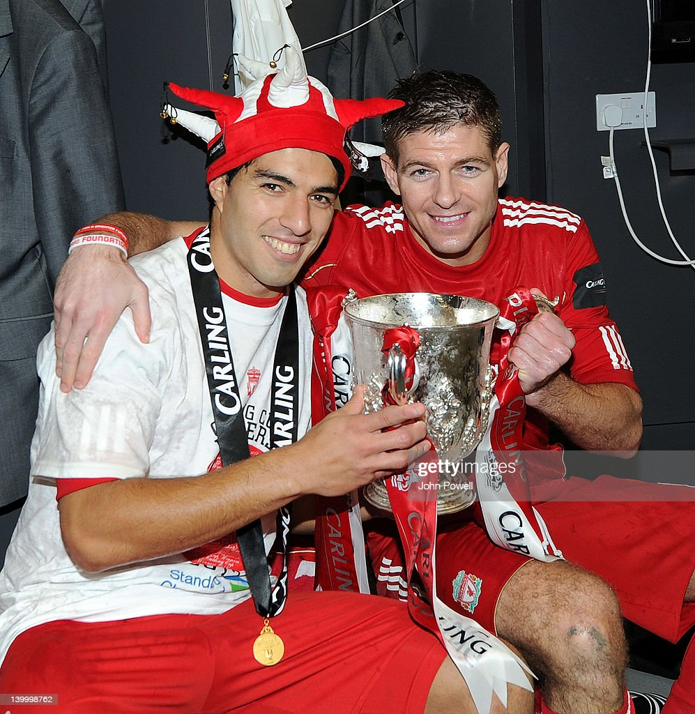 MINIMUM FEES APPLY - 150GBP OR LOCAL EQUIVALENT, PER IMAGE) (THE SUN OUT, THE SUN ON SUNDAY OUT) Luis Suarez and Steven Gerrard of Liverpool celebrate with the trophy at the end of the Carling Cup Final match between Liverpool and Cardiff City at Wembley Stadium on February 26, 2012 in London, England.